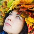 Stock Photo: Womwith leaves on head look up