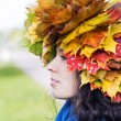 Stock Photo: Woman with maple leaves on head