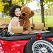 Stock Photo: Womwith bear toy in retro car