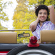 Stock Photo: Woman with wide smile at retro car