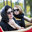 Women with dark glasses adjust spotted scarf — Stockfoto