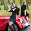 Stock Photo: Women in black relay on car front