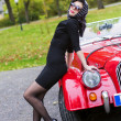 Stock Photo: Womin black posing on retro car front