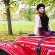 Womin skirt on red car cowling — Stock Photo #33719113