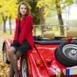 Woman in red and car at park — Stock fotografie