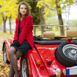Woman in red and car at park — ストック写真