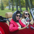 Women in black on red retro car — Stock Photo