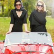 Stock Photo: Young women on red retro car on ride