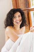 Smiling woman under blanket bite hair perm — Stock Photo