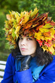 Thoughtful woman with maple leaves on head — Stock Photo