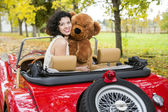 Woman with bear toy in retro car — Stock Photo