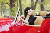 女性の車のホイールを保持して振り返る — ストック写真