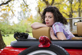 Woman relay at retro car seat back — Stock Photo