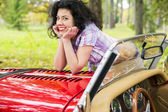 Woman relay elbows on retro car cowling — Stock Photo