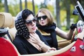 Women with dark glasses adjust spotted scarf — Zdjęcie stockowe
