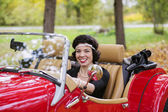 Smiling young woman after red car wheel — Stock Photo