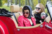 Mulheres no carro vermelho retrô parecem satisfeitas — Fotografia Stock