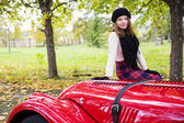 Woman in skirt on red car cowling — Stock Photo