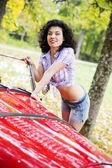Woman in shirt posing on retro car side — Stock Photo