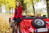 Woman in red and car at park — Stock Photo