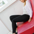 Woman on low red sofa from leather — Stock Photo #39546717