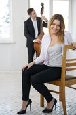 Woman on wooden chair and contrabas player — Стоковое фото