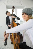 Woman backwards on chair and contrabas player — Stock Photo