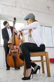 Woman backwards on chair listen contrabass play — Stockfoto