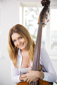 Woman hold on contrabass with both hands — Stock Photo