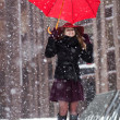 Woman with umbrella enjoy snowfall on street — Stock Photo