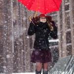 Woman with umbrella enjoy snowfall on street — Stock Photo