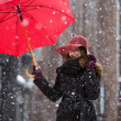 Woman with umbrella on snowy street — Stock Photo #40024085