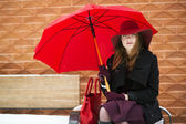 Woman with red purse and umbrella — Stock Photo