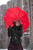Woman holding umbrella and snowfall freez — Stockfoto