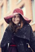 Woman at winter street under light snowfall — Stockfoto