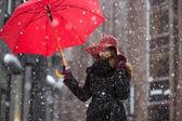 Woman with umbrella on snowy street — Stock Photo