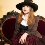 Beautiful woman and expensive soft renaissance furniture — Stock Photo