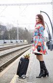 Mulher espera trem com mala e flores — Foto Stock