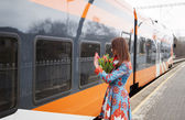 Woman with flowers salute to train passanger — 图库照片