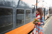 Woman with flowers adopt finaly come train — Stok fotoğraf