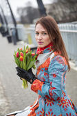 Woman waiting train with bundle of flowers — Photo