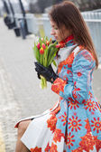 Woman waiting train look at flowers — Stock Photo
