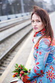 Woman waiting train with flowers at hand — Stock Photo