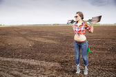 Woman holding sharp shovel on weak shoulders — Stock Photo