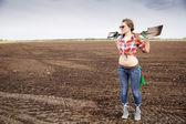 Woman holding sharp shovel on weak shoulders — Stock Photo