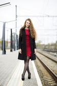 Woman at red dress with crossed legs — Stock Photo