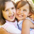 Two Young Girls Giving One Another Hug In Summer Field — Foto de Stock   #24440393