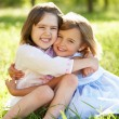 Stock Photo: Two Young Girls Giving One Another Hug In Summer Field