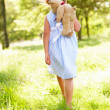 Stock Photo: Young Girl Walking Through Summer Field Carrying Teddy Bear