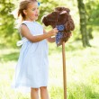 Stock Photo: Young Girl Playing With Hobby Horse In Summer Field
